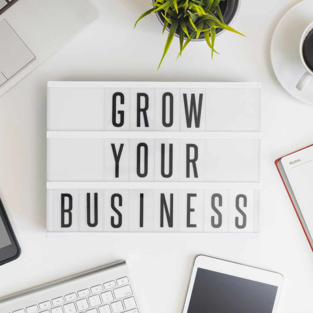 Sign on a desk with Grow Your Business written