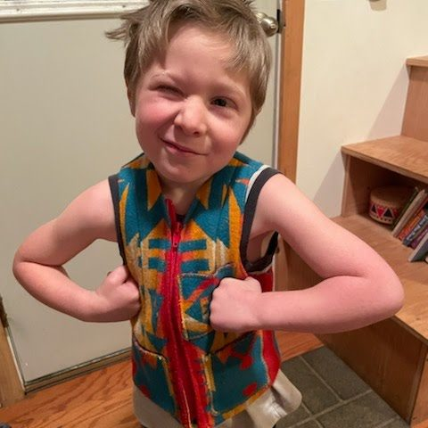 Young boy standing with hands in fists on hips winking at camera