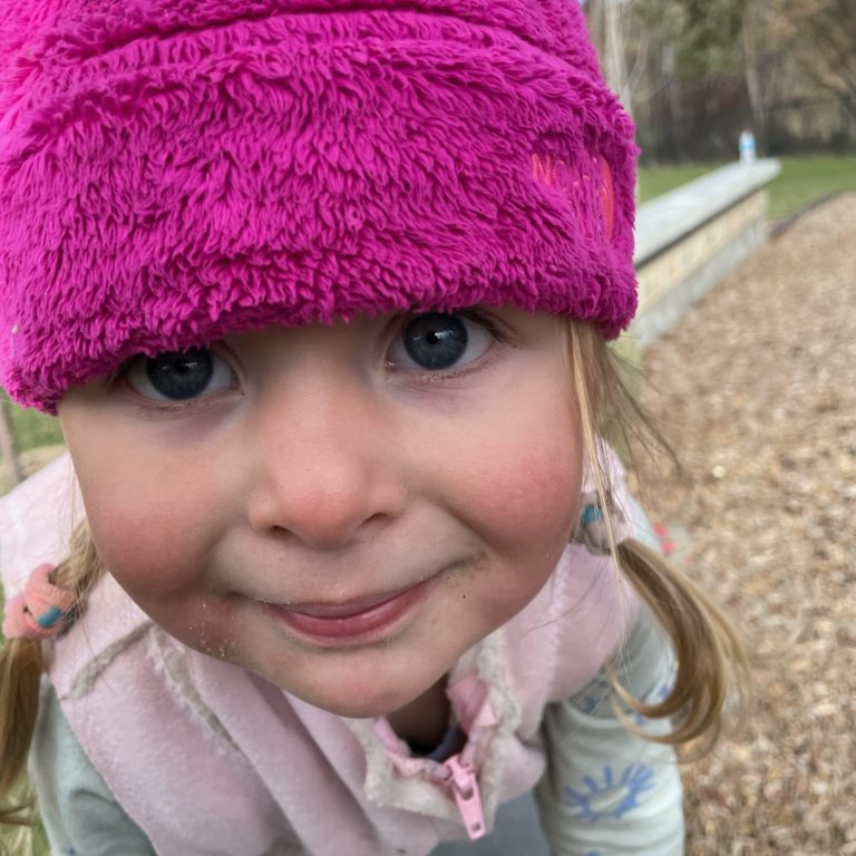 Toddler with pink hat smiling at camera