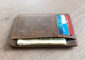 Leather wallet with cards and money inside sitting on a wooden table